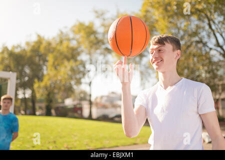 Smiling young male basketball player balancing basketball on finger - Stock Photo