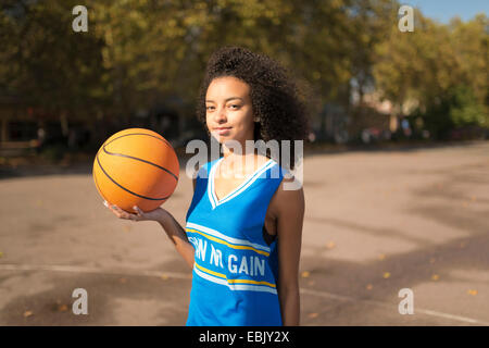 Portrait young female basketball player holding up basketball - Stock Photo