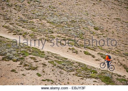 Male mountain biker cycling up steep dirt track, Reykjadalur valley, South West Iceland - Stock Photo