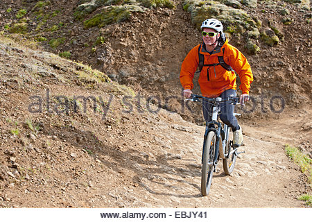 Young male mountain biker cycling up dirt track, Reykjadalur valley, South West Iceland - Stock Photo