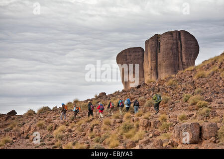 hiking group in front of rock formation, Morocco, Souss-Massa-DaraÔ, Djebel Sarhro - Stock Photo