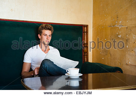Young man sitting at cafe table reading newspaper - Stock Photo