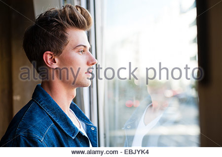 Young man gazing through cafe window - Stock Photo