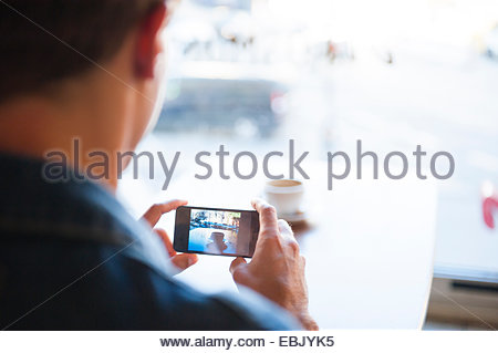 Over shoulder view of young man taking photographs on smartphone in cafe - Stock Photo