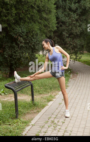 Young female runner stretching legs on park bench - Stock Photo