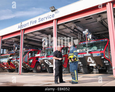 Officer and fireman in front of fire engines in airport fire station - Stock Photo