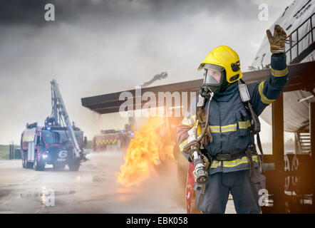 Portrait of fireman in front of simulated fire at airport training facility - Stock Photo