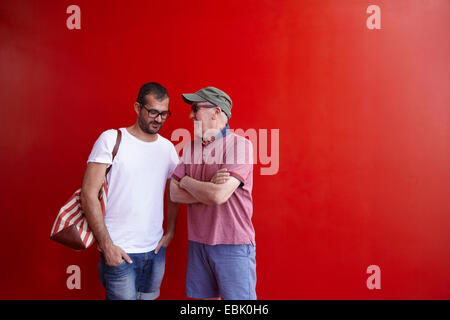 Mid adult man and senior man talking, standing against red background - Stock Photo