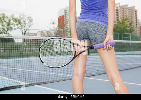 Cropped rear view of young female tennis player on tennis court - Stock Photo