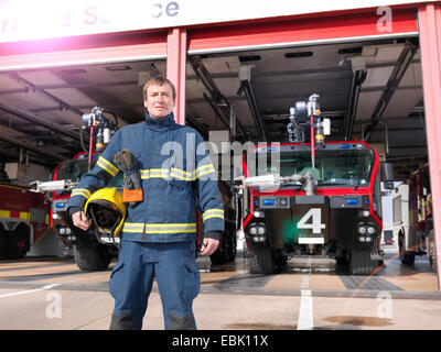 Portrait of fireman in front of fire engines in airport fire station - Stock Photo