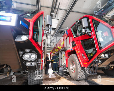 Firemen in discussion between fire engines in airport fire station - Stock Photo