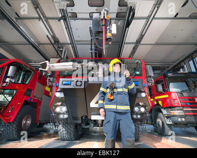 Fireman using walkie talkie in front of fire engines in airport fire station - Stock Photo