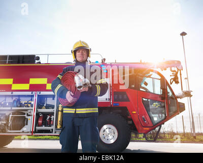 Portrait of fireman in front of fire engine in airport fire station - Stock Photo