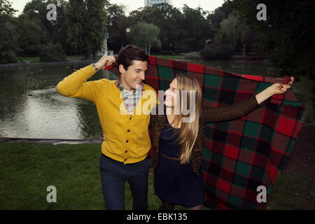 Young couple holding up blanket in park - Stock Photo