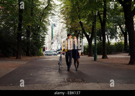 Young couple strolling in tree lined park - Stock Photo