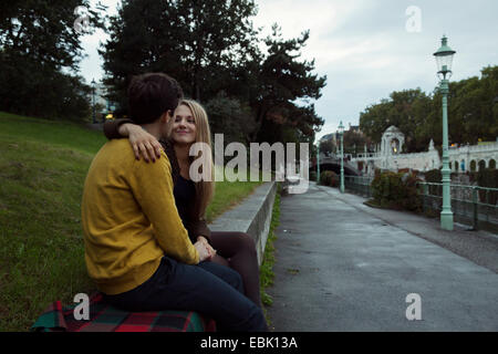 Young couple sitting face to face on park wall - Stock Photo
