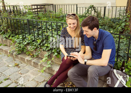 Young couple sitting on wall looking down at smartphone - Stock Photo