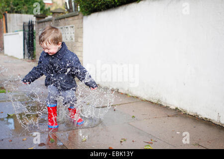 Male toddler in red rubber boots splashing in sidewalk puddle - Stock Photo