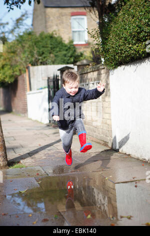 Male toddler in red rubber boots jumping into sidewalk puddle - Stock Photo