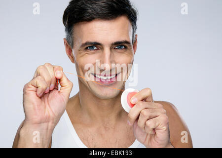 Portrait of a happy man with dental floss over gray background - Stock Photo