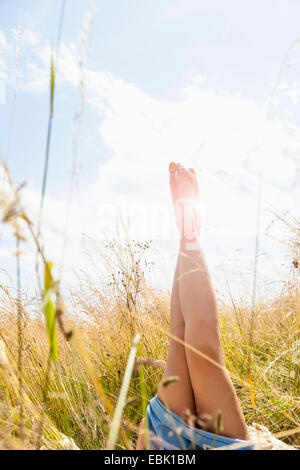 Young womans bare legs in field of long grass - Stock Photo