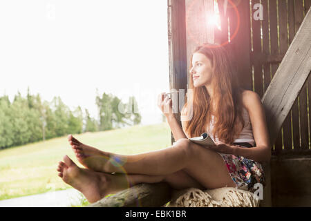 Young woman sitting in barn with notebook - Stock Photo