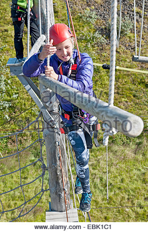 Girl holding rope on high rope course - Stock Photo