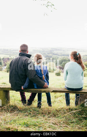 Father sitting with daughters looking at view - Stock Photo
