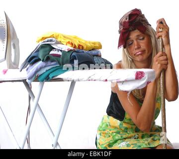 tired and bored blonde young housewife leaning on broomstick is sitting in front of ironing board with pile of clothes - Stock Photo