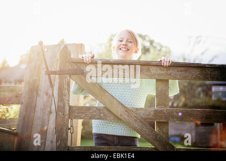 Girl looking over wooden gate - Stock Photo