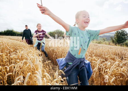 Girl running through field with arms out - Stock Photo