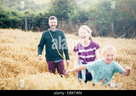 Father with two girls running through field - Stock Photo