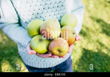 Girl holding homegrown apples in hands - Stock Photo