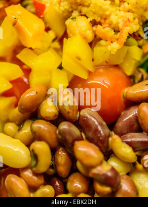 Healthy vibrant salad of mixed brown and yellow beans with tomato, yellow pepper and couscous. - Stock Photo