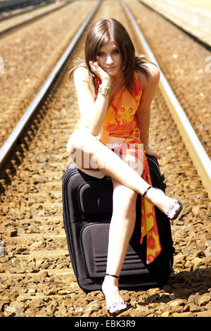 young woman sitting on railway track with luggage, Germany - Stock Photo