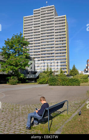boy sitting on bench and playing gameboy, tower block in background, Germany, Chorweiler, Cologne - Stock Photo