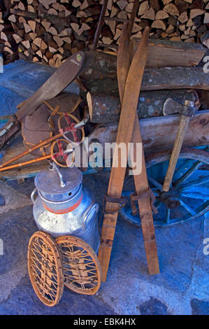 historical ski equipment and milk can with firewood piles in front of a mountain hut, France - Stock Photo