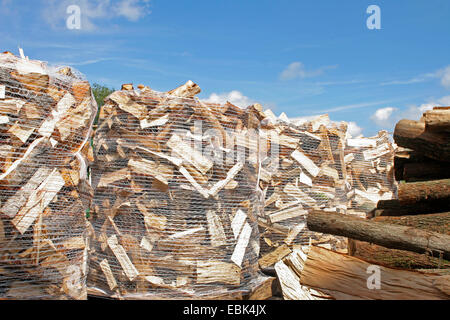 firewood working, storage area with sacks of firewood, Germany - Stock Photo