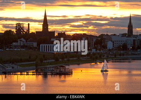 sailing boats on Lake Phoenix with the silhouette of the district Hoerde at sunset, Germany, North Rhine-Westphalia, - Stock Photo