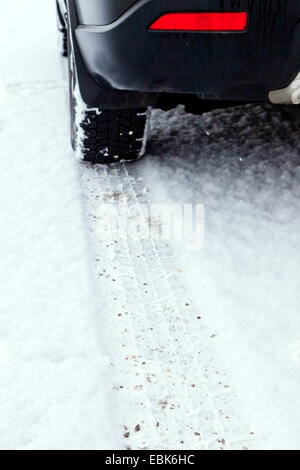 trace of a winter tyre of a passenger car on the snow-covered lane of a road - Stock Photo