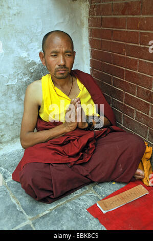 monk sitting praying on the floor in a corner of the stupa of Bouddhanath, one of the holiest Buddhist sites of - Stock Photo