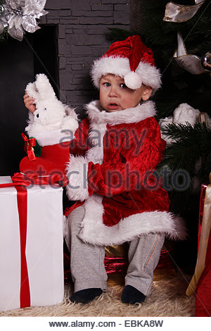 crying baby Santa Claus by the fireplace - Stock Photo