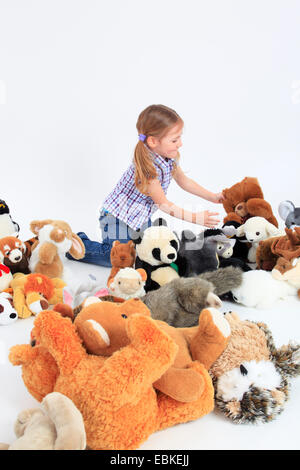little happy girl playing with soft toys - Stock Photo