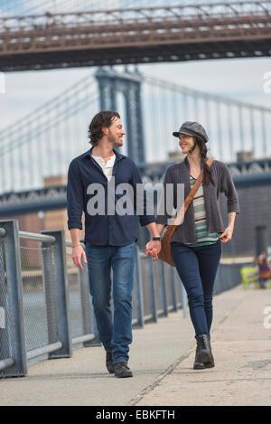 USA, New York State, New York City, Brooklyn, Couple walking on promenade, Brooklyn Bridge in background - Stock Photo