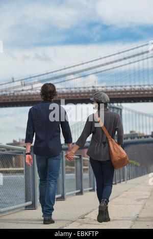 USA, New York State, New York City, Brooklyn, Rear view of couple walking on promenade, Brooklyn Bridge in background - Stock Photo