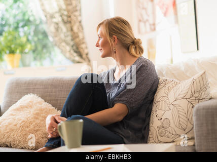 Woman sitting on sofa in living room - Stock Photo