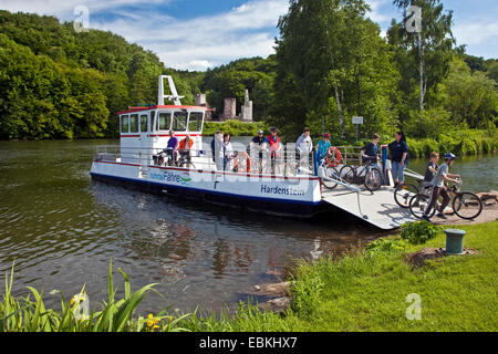 ferry boat with cyclists crossing Ruhr river, castle ruin Hardenstein in background, Germany, North Rhine-Westphalia, - Stock Photo