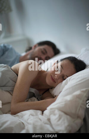 Couple sleeping together in bed at night - Stock Photo