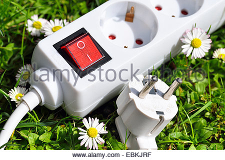 socket outlet on grass, symbol for green electricity, Germany - Stock Photo
