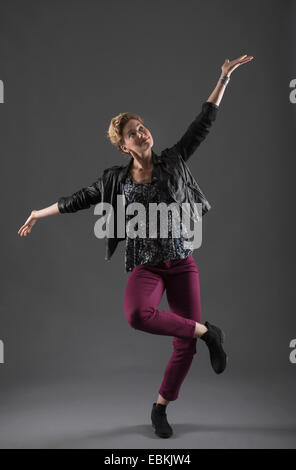 Studio shot of cheerful woman with arms raised - Stock Photo